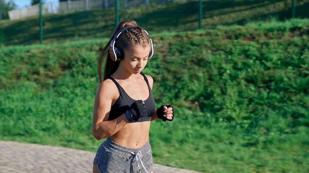 Trening biegaczy na stadionie w słuchawkach