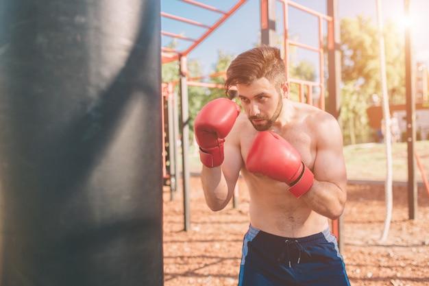 Trening bokserski młodego człowieka. bokser ćwiczenia koncepcji boksu sportowego. bokser cios ręką worek treningowy.