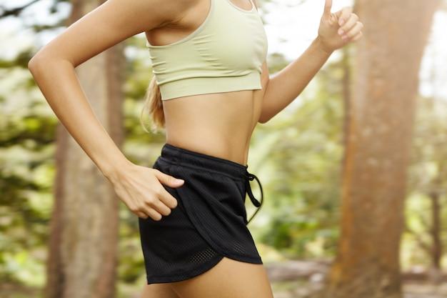 Trening cardio dla biegaczy. przycięte ujęcie nierozpoznawalnej biegaczki w szybkim tempie przedstawiające sportowy stanik i czarne spodenki.
