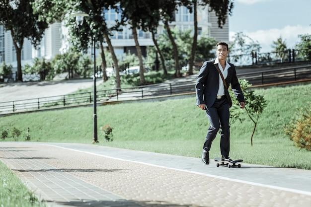 Trening codzienny. aktywny student płci męskiej, jazda na deskorolce i ubrany w garnitur