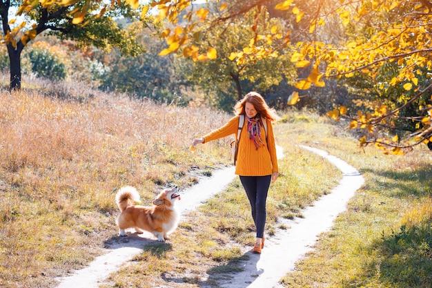 Trening - dziewczyna i pies corgi spacerują po parku