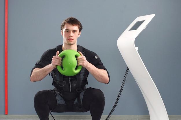 Trening fit man w stroju ems z balem medycznym.