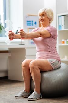 Trening fitness. aktywna starsza kobieta ćwiczy siedząc na piłce fitness