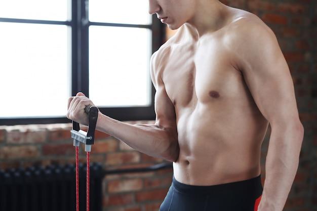 Trening fitness człowieka. półnagi mężczyzna robi rozciąganie w domu