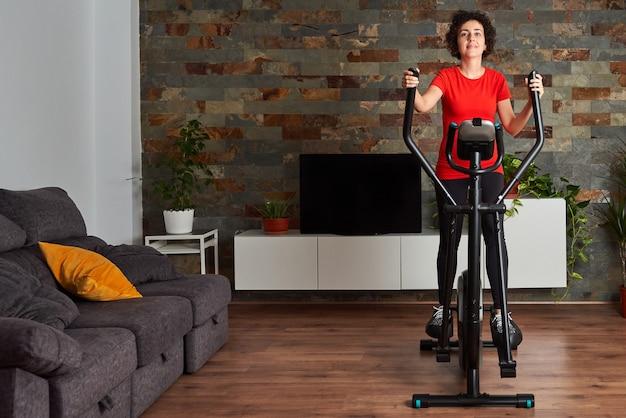 Trening fitness kobieta w domu trening na inteligentnym orbitreku w pomieszczeniu