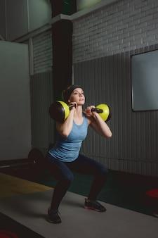 Trening fitness kobiety przez kettlebell. fit młoda dama robi ćwiczenia crossfit.
