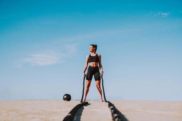 Trening funkcjonalny na plaży, sprawna i wysportowana kobieta uprawiająca sport na świeżym powietrzu