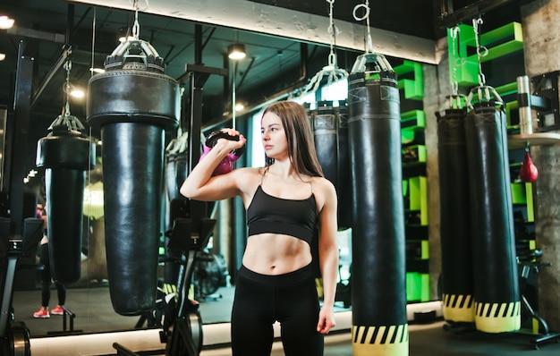 Trening funkcjonalny. sprawności fizycznej kobieta robi ćwiczyć z kettlebell.