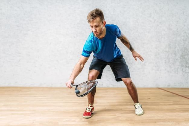 Trening gry w squasha, mężczyzna gracz z rakietą