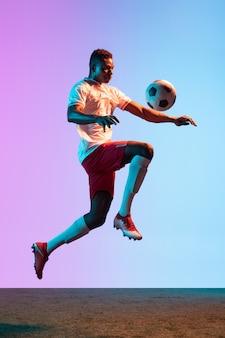 Trening jednego profesjonalnego piłkarza w piłkę nożną na białym tle na ścianie gradientowej