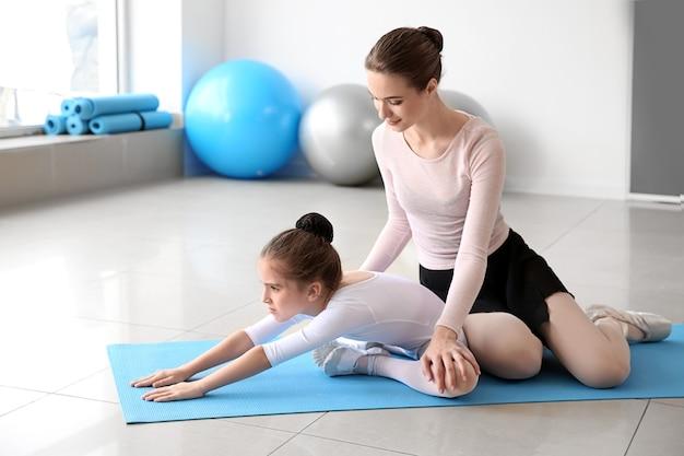 Trening małej baleriny z trenerem w studiu tańca