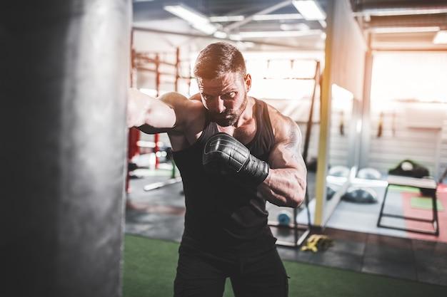 Trening męskiego boksera z workiem treningowym w ciemnej hali sportowej.