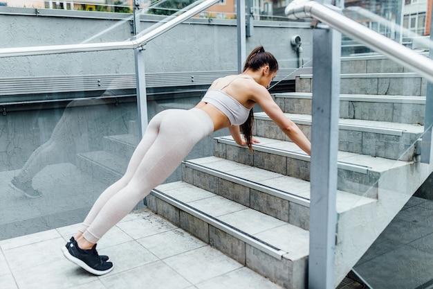 Trening miejski fitness kobieta robi nogi podwyższone pompki na schodach parku miejskiego. zmotywowana lekkoatletka ciężko trenująca.