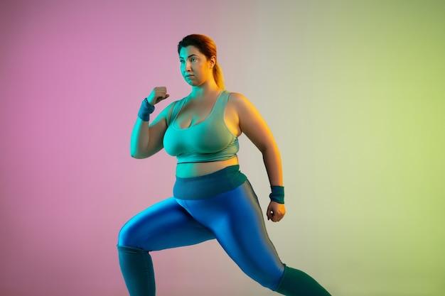 Trening młodej modelki rasy kaukaskiej plus size na gradientowej fioletowo zielonej ścianie w neonowym kolorze. wykonywanie ćwiczeń rozciągających.