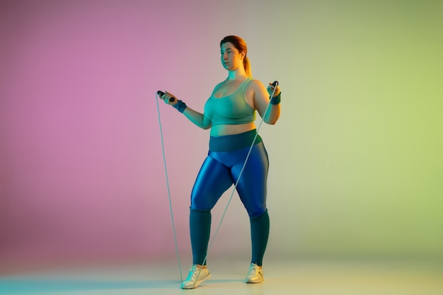 Trening młodej modelki rasy kaukaskiej plus size na gradientowej fioletowo zielonej ścianie w neonowym kolorze. wykonywanie ćwiczeń treningowych ze skakanką.