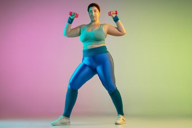 Trening młodej modelki rasy kaukaskiej plus size na gradientowej fioletowo zielonej ścianie w świetle neonowym. wykonywanie ćwiczeń treningowych z ciężarami. pojęcie sportu, zdrowego stylu życia, pozytywnego ciała, równości.