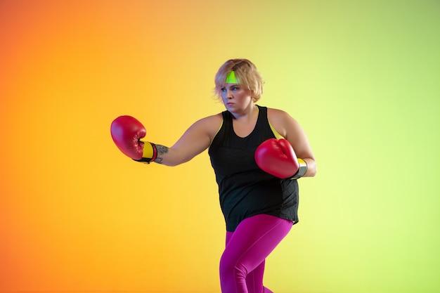 Trening młodej modelki rasy kaukaskiej plus size na gradientowej pomarańczowej ścianie w świetle neonowym.