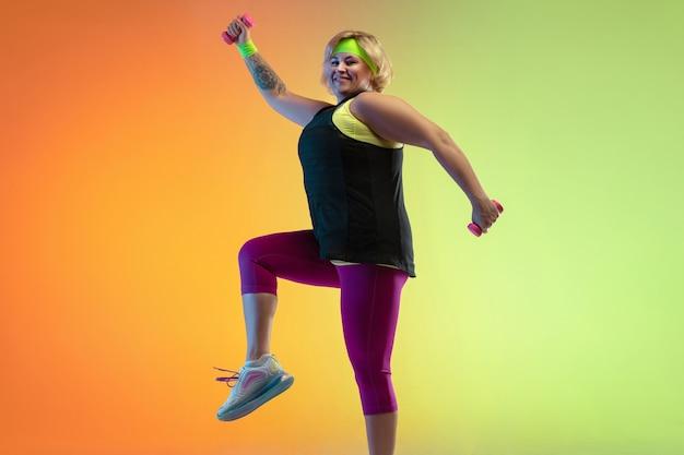 Trening młodej modelki rasy kaukaskiej plus size na pomarańczowym tle gradientu w świetle neonowym. wykonywanie ćwiczeń treningowych z ciężarami. pojęcie sportu, zdrowego stylu życia, pozytywnego ciała, równości.