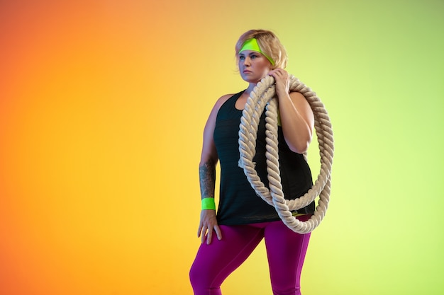 Trening młodej modelki rasy kaukaskiej plus size na pomarańczowym tle gradientu w świetle neonowym. wykonywanie ćwiczeń treningowych z linami. pojęcie sportu, zdrowego stylu życia, pozytywnego ciała, równości.