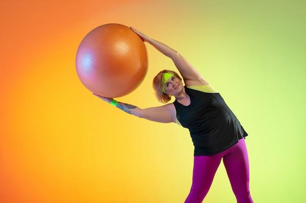 Trening młodej modelki rasy kaukaskiej plus size na pomarańczowym tle gradientu w świetle neonowym. wykonywanie ćwiczeń treningowych z piłką fit. pojęcie sportu, zdrowego stylu życia, pozytywnego ciała, równości.