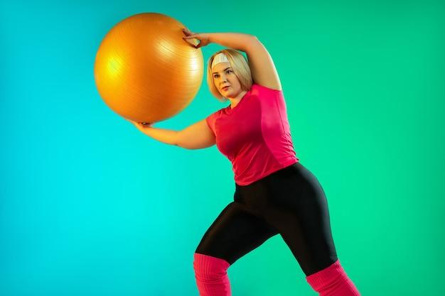 Trening młodej modelki rasy kaukaskiej plus size na zielonym tle gradientu w świetle neonowym. wykonywanie ćwiczeń treningowych z fitballem. pojęcie sportu, zdrowego stylu życia, pozytywnego ciała, równości.