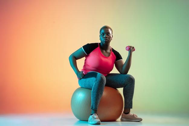 Trening młodych afro-amerykańskich modelek plus size na ścianie gradientowej w świetle neonowym.