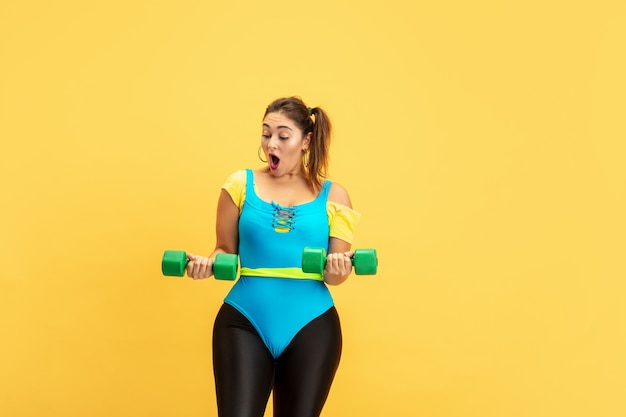 Trening młodych kaukaski plus size modelki na żółtej ścianie. miejsce. pojęcie sportu, zdrowego stylu życia, pozytywnego ciała, mody, stylu. stylowa kobieta emocjonalne ćwiczenia z ciężarami.