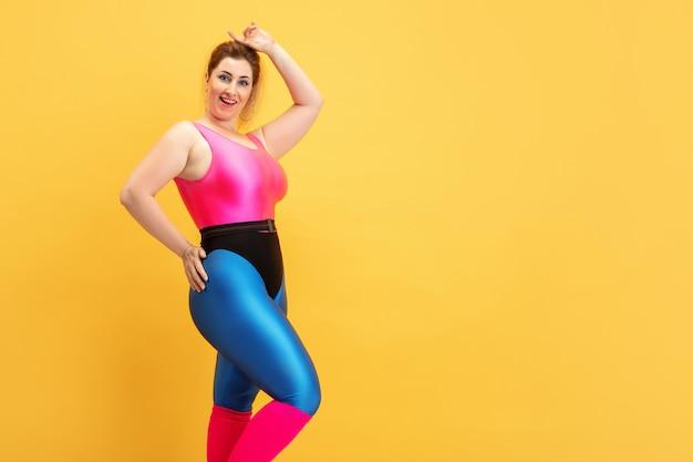 Trening młodych kaukaski plus size modelki na żółtej ścianie. miejsce. pojęcie sportu, zdrowego stylu życia, pozytywnego ciała, mody, stylu. stylowa kobieta pozowanie pewnie i fajnie.