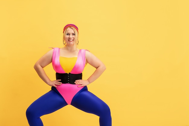 Trening młodych kaukaski plus size modelki na żółtej ścianie. miejsce. pojęcie sportu, zdrowego stylu życia, pozytywnego ciała, mody, stylu. stylowa kobieta, rozciąganie i uśmiechanie się.