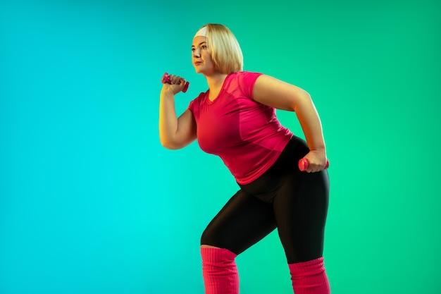 Trening młodych modelek rasy kaukaskiej plus size na zielonym tle gradientu w świetle neonu. wykonywanie ćwiczeń treningowych z ciężarami. pojęcie sportu, zdrowego stylu życia, pozytywnego ciała, równości.