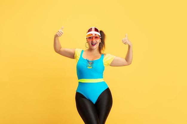Trening młodych modelek rasy kaukaskiej plus size na żółto