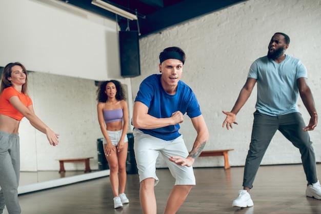 Trening, nastrój. wesoły facet z tatuażem na ramieniu tańczy z przyjaciółmi na treningu tańca