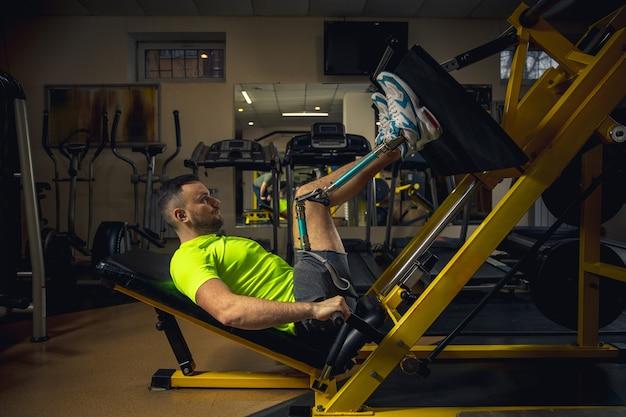 Trening niepełnosprawnego mężczyzny w sali gimnastycznej ośrodka rehabilitacyjnego