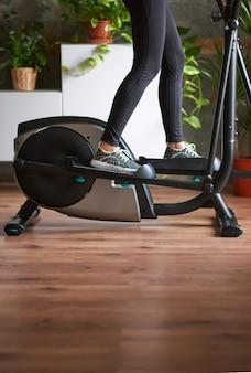 Trening nóg kobiety na inteligentnym trenażerze eliptycznym w pomieszczeniu w domu w świetle dziennym z naturalnym światłem