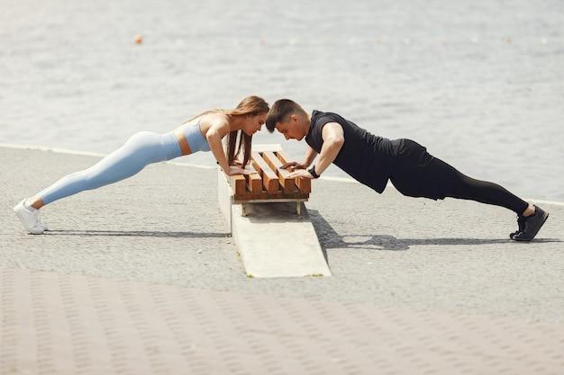 Trening par. ludzie w strojach sportowych. para w letnim parku