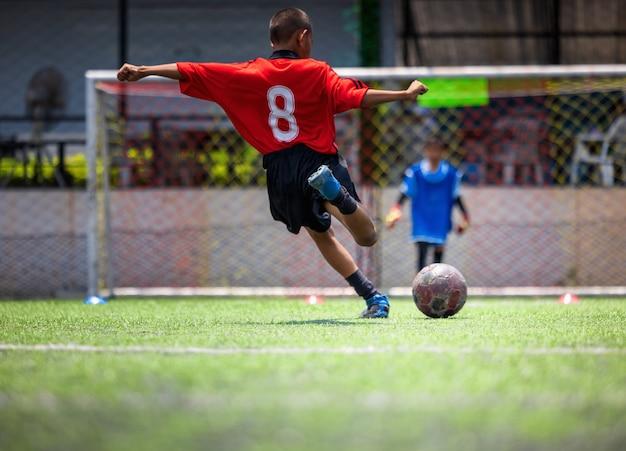Trening piłki nożnej dla dzieci. trener wyjaśniający plan gry. młodzi chłopcy doskonalą umiejętności piłkarskie w lokalnej tajlandii