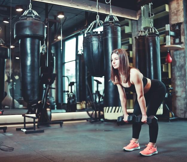 Trening pośladków. dysponowana kobieta w sport odzieży jest robić deadlift ćwiczeniu z dumbbell przy gym