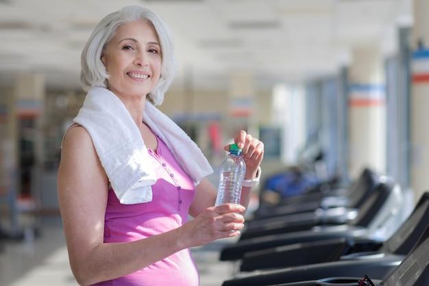 Trening progresywny. piękna szczęśliwa starsza kobieta uśmiecha się i wody pitnej podczas odpoczynku po sporcie.