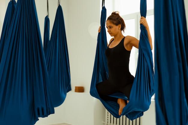 Trening rozciągający. zdrowy tryb życia. młoda piękna dziewczyna w czarnym mundurze robi ćwiczenia rozciągające. akroyoga, joga, fitness, trening, sport.