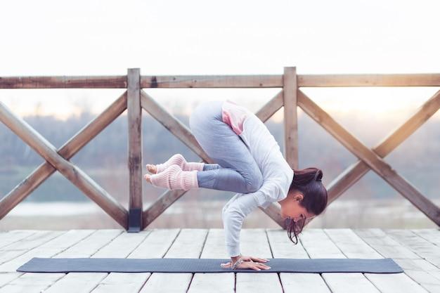 Trening siłowy kobiety jogi na macie do ćwiczeń robi ćwiczenia jogi w przyrodzie