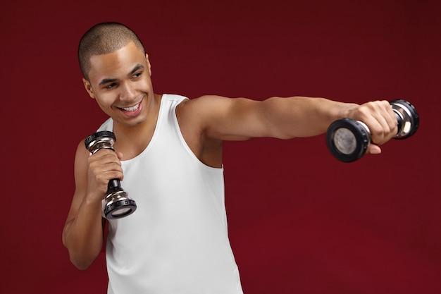 Trening siłowy. obraz energicznego szczęśliwego młodego faceta rasy mieszanej w białym podkoszulku podnoszącym hantle na siłowni, budującym atletyczne muskularne ciało, o wesołym wyglądzie, cieszącym się procesem ćwiczeń