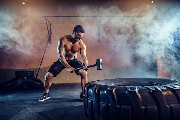 Trening sportowy na wytrzymałość, mężczyzna uderza dużym młotkiem do opon. trening koncepcyjny.