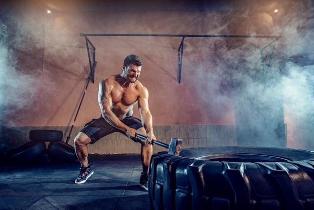 Trening sportowy na wytrzymałość, mężczyzna uderza młotkiem. trening koncepcyjny.