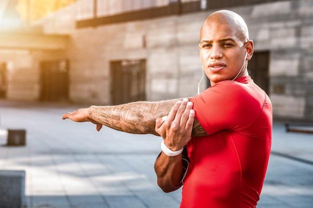 Trening sportowy. poważny miły człowiek robi różne ćwiczenia fizyczne podczas treningu
