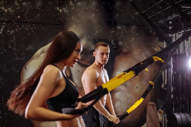 Trening sportsmenki z opaską trx z trenerem w centrum sportowym
