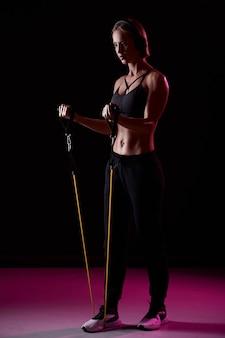 Trening sportsmenki z taśmami oporowymi na czarnym tle