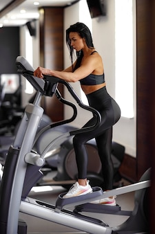 Trening w siłowni trener dziewczyna fitness pracuje na maszynie krok