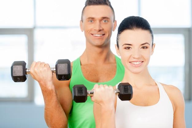 Trening z hantlami. para podnosząca hantle na siłowni i uśmiechająca się do kamery