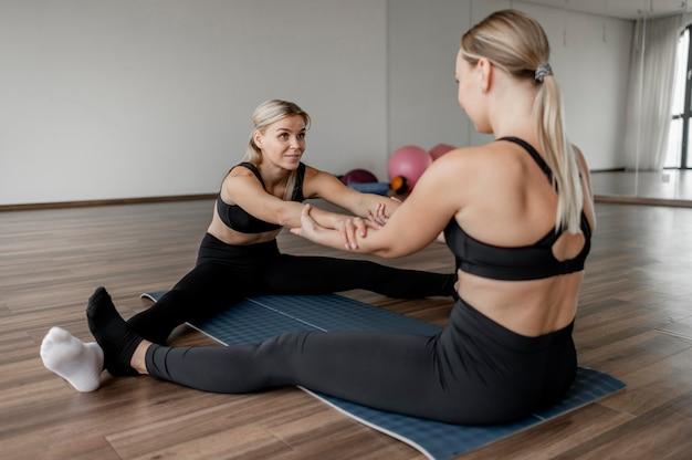Trening z osobistym trenerem i klientem przez ramię