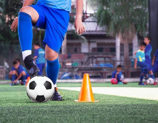 Treningi piłkarskie młodzieżowe ćwiczą przy użyciu stożków